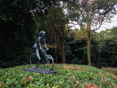 Stone statue of girl on bike amidst greenery